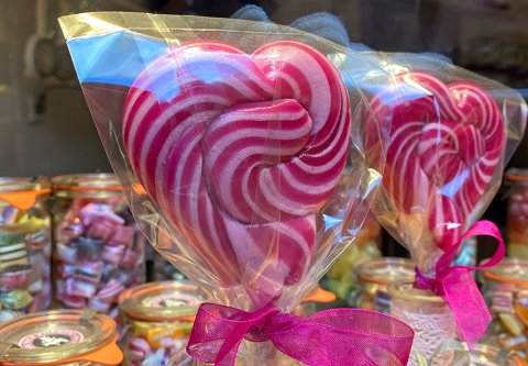 Zwei große rote Lutscher in Herzform stehen im Schaufenster der Bremer Bonbon Manufaktur