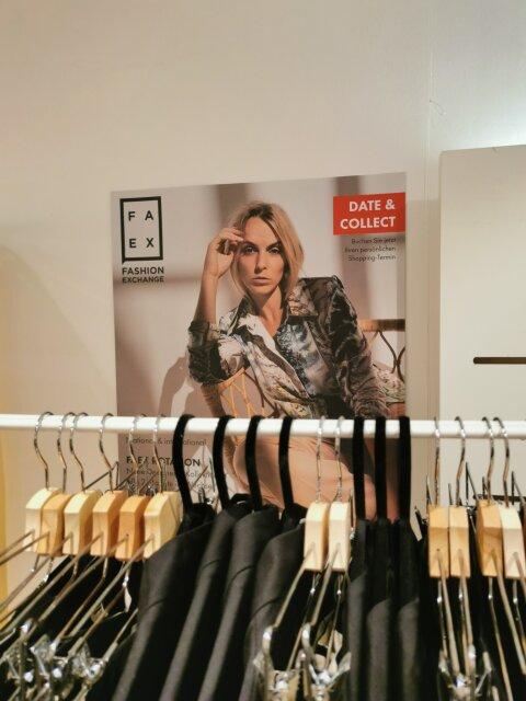 Nahaufnahme eines Kleiderständers mit einem Werbeplakat an der Wand im Pop-up-Store FAEX