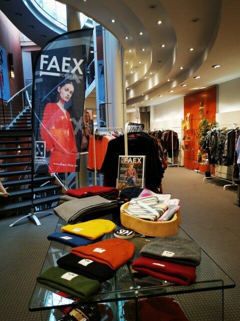 Tisch mit Mützen und Kleiderständer mit Kleidung im Pop-up-Store FAEX, im Hintergrund ist ein Rollup zu sehen
