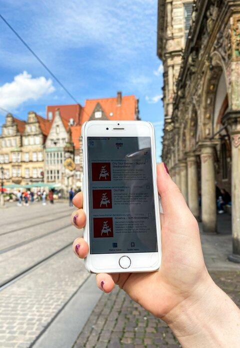 Ein Handy wird ins Bild gehalten. Im Hintergrund ist der Marktplatz zu sehen.