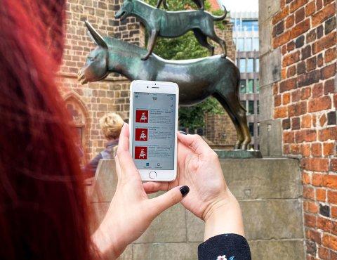 Eine Frau hält ein Handy in die Kamera. Im Hintergrund sind die Stadtmusikanten zusehen.