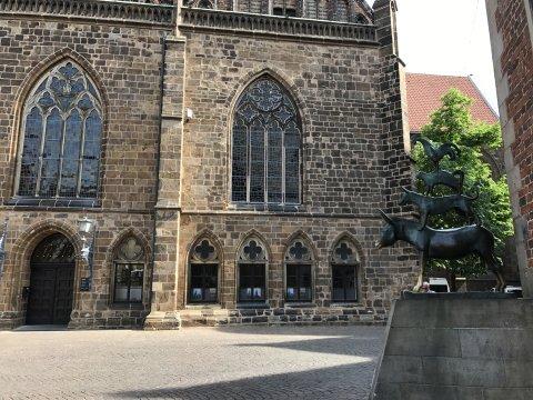 Die Bremer Stadtmusikanten rechts platziert mit Gebäuden im Hintergrund.