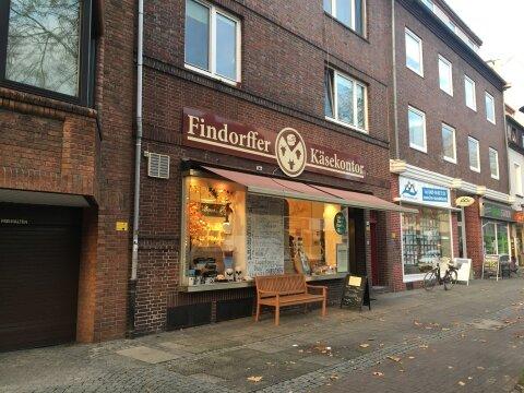 Der Findorffer Käsekontor von außen. Vor der Tür steht eine Holzbank. Im Schaufenster sind kleine Geschenkartikel ausgestellt.