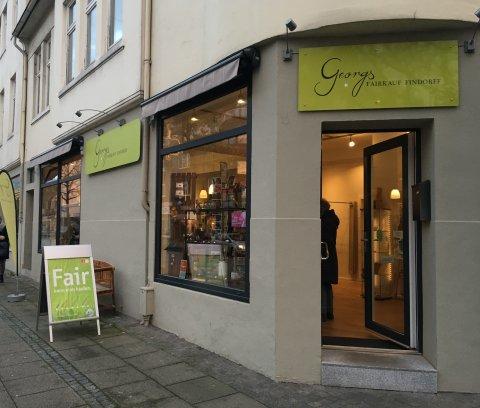 """Der Fairtrade Laden """"Georgs Fairtrade"""" in der Außenansicht. Ein grünes Schild hängt über der Eingangstür auf dem """"Georgs Fairkauf Findorff"""" steht."""