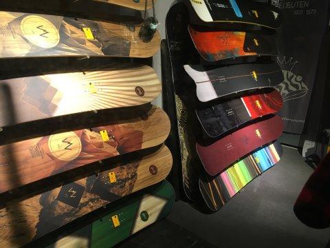 Diverse Snowboard-Bretter hängen an der Wand und werden präsentiert.