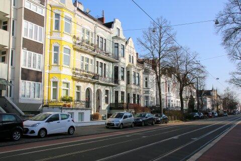 Mehrere Altbremer Häuser stehen aneinander gereiht. Davor parken Autos und die Sonne scheint.