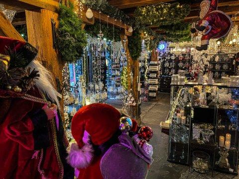 Der Laden von innen. Es funkelt und glitzert überall. Es hängen Lichterketten und Kugeln im Raum. Zwei Weihnachtsmännerfiguren stehen im Bild.