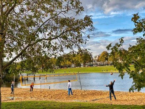 Zu sehen ist das Volleyballfeld am Cafè Sand, auf dem mehrere Personen Volleyball spielen.