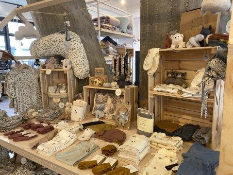 Zu sehen sind Babyklamotten, Kuscheltiere und Kissen aus dem Laden Kind der Stadt in Bremen.