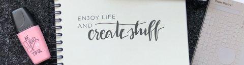 """Malutensilien, wie Radiergummi und Stifte und ein Notizheft mit der Aufschrift """"enjoy life and create stuff"""""""