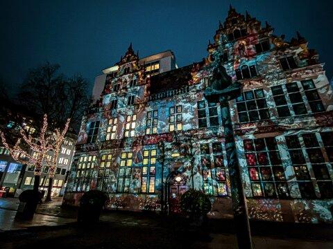 Die Handwerkskammer wird von einem Lichtspiel angeleuchtet. Es sind weihnachtliche Motive auf der Fassade zu sehen.