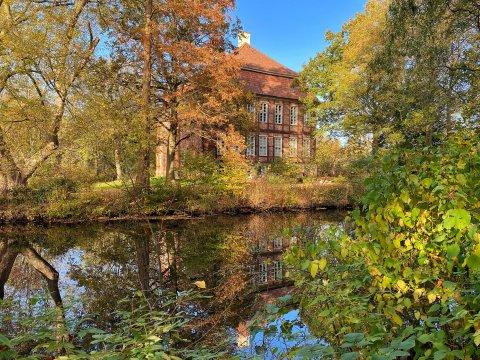 Das von herbstlichen Bäumen und Büschen sowie einem Gewässer umgebene Schloss Schönebeck an einem sonnigen Herbsttag.