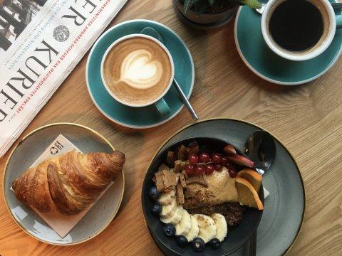 Ein Frühstückstisch mit einem Croissant, einer Bowl mit verschiedenem Obst, ein Cappuccino und ein Kaffee stehen auf einem Holztisch. Seitlich sieht man einen Weser Kurier liegen.