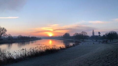 Über dem Werdersee geht gerade die Sonne auf. Die Wiesen sind gefroren.