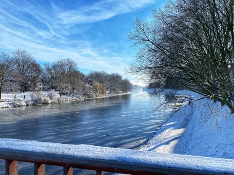 Der Blick geht über ein Gelände auf den Werdersee. Er ist zugefroren. Die Natur am Rand ist mit Schnee bedeckt und man sieht Leute spazieren.