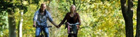 Ein Paar fährt mit dem Fahrrad durch einen Park