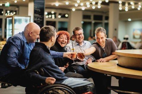 Auf dem Bild sind Menschen mit Behinderung in Interaktion mit ihren Assistenzen zu sehen.