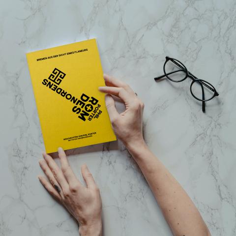 Der gelbe Einband des Buches wird von zwei Händen ins Bild gehalten. Daneben liegt eine schwarze Brille.