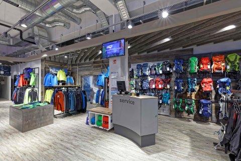 Eine Service Station im Laden mit Rucksäcken und Kleidung im Hintergrund.