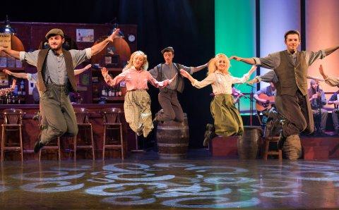 Männer und Frauen tanzen auf einer Bühne, die einen Pub imitiert.