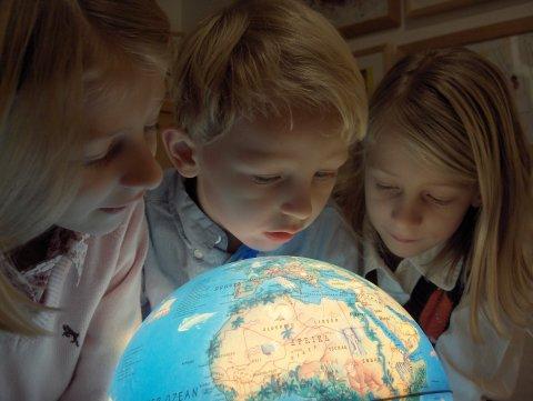 Drei Schüler betrachten einen leuchtenden Globus