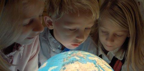 Drei Kinder betrachten einen leuchtenden Globos