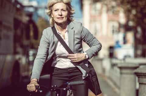 Frau sitzt im Anzug auf dem Fahrrad