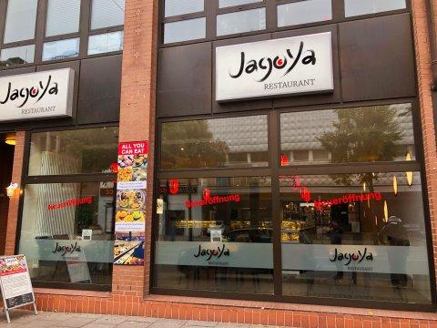 """Das Sushi-Restaurant von außen. Es klebt ein Sticker an der Scheibe, auf dem """"Neueröffnung"""" steht."""