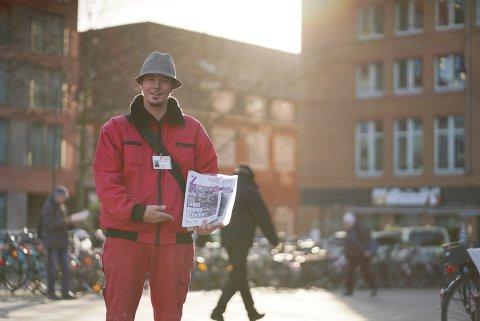 Mann in roter Kleidung, der die Zeitschrift der Strasse in den Händen hält. Im Hintergrund sind verschwommen Passant*innen zu sehen.