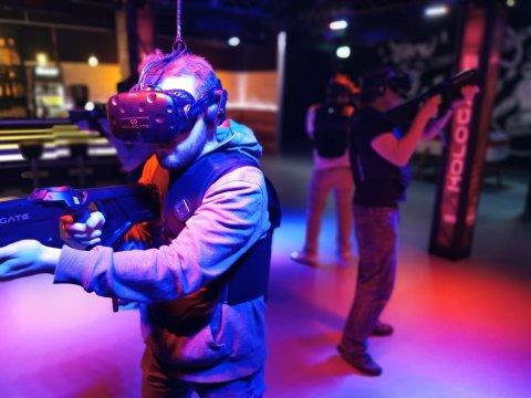 Ein Mann steht in einem bunt beleuchteten Raum und trägt eine Virtual Reality-Brille.