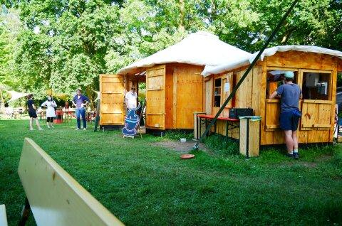 Pavillon-Jurte im Neustadtspark aus hellem Holz auf grünem Rasen.