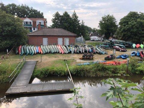 Viele Kanu's liegen aneinander gereiht auf einem Landstück am Wasser.