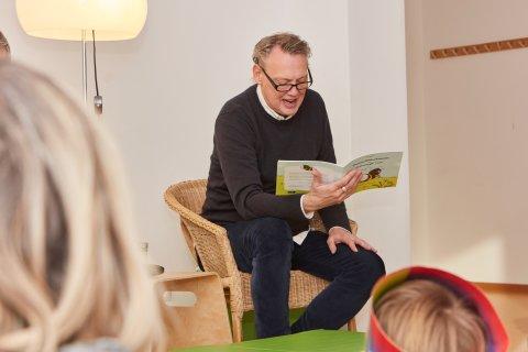 SOS-Kinderdorf Botschafter Dirk Böhling sitzt auf einem Stuhl und liest Kindern ein Buch vor.