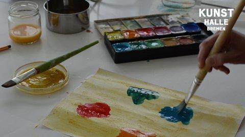 Auf einem Tisch befinden sich Wasserfarben und verschiedene Malutensilien. Eine Hand hält einen Pinsel und malt ein Bild.