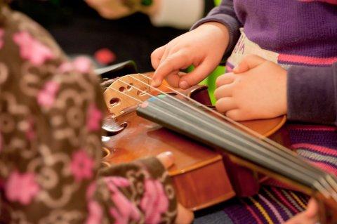 Kleine Kinderhände zupfen an den Saiten einer Geige (Quelle: Bremer Philharmoniker)