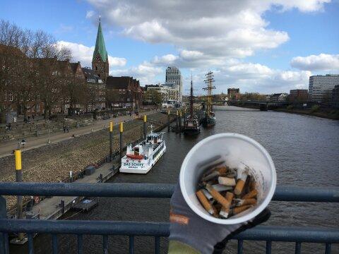Zu sehen ist die Bremer Schlachte mit einigen Gebäuden. Eine Hand mit Handschuh hält einen Becher mit Zigarettenkippen in die Kamera.