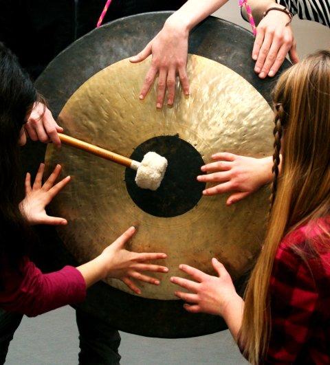 Kinder berühren mit ihren Händen und einem Gongschlägel einen Gong und erzeugen Klänge.