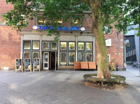 Eine Außenaufnahme des Fischrestaurants namens Knurrhahn. Vor dem roten Backsteingebäude steht ein großer Baum.
