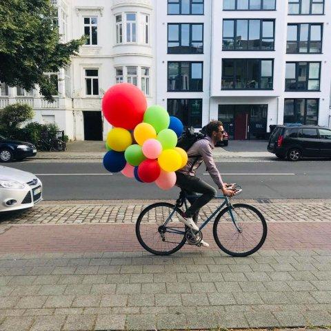 Mann fährt auf einem Rennrad, an dem viele bunte Luftballons befestigt sind