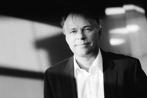 Ein schwarz-weiß Bild von dem Dirigenten Thomas Hengelbrock. Er hat ein weißes Hemd und ein schwarzes Sakko an und schaut in die Kamera.