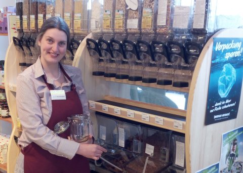 Verkäuferin schaut in die Kamera, während sie ein Glas mit Körner füllt.