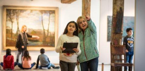 Zwei Mädchen betrachten etwas in einem Museum