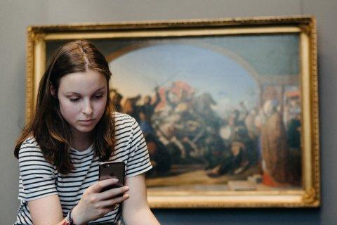 Eine Frau sitzt mit dem Rücken zu einem Gemälde und schaut auf ihr Smartphone.