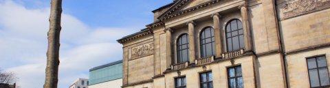 Die Kunsthalle Bremen von außen mit Osterglocken und blauem Himmel.