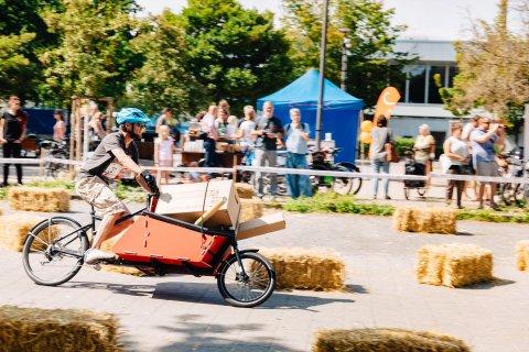Ein Mann fährt mit dem Lastenrad an Heuhindernissen vorbei. Zuschauer sehen im Hintergrund zu.