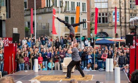 Ein Artist hält eine Artistin in die Luft.