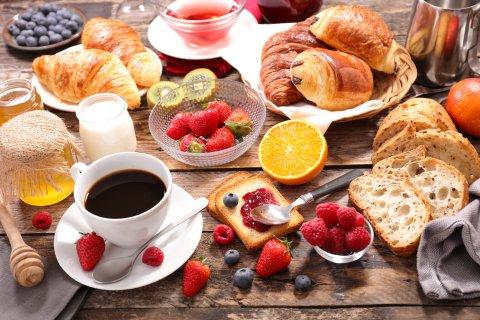 Ein großes leckeres Frühstück mit Kaffee, Croissant und verschiedenen Obstsorten