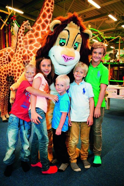 Kinder werden von einem Mensch im Löwenkostüm umarmt.