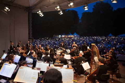 Ein spielendes Orchester vor einem Publikum, das Wunderkerzen in die Luft hält.