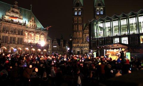 Zahlreiche Menschen mit Laternen vor dem beleuchteten Rathaus